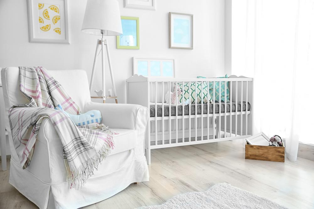 nursery with white walls and slipcovered rocker